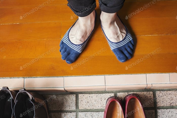 A man's feet in socks by a row of shoes.