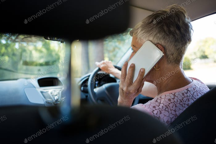 Senior woman talking on mobile phone while driving a car