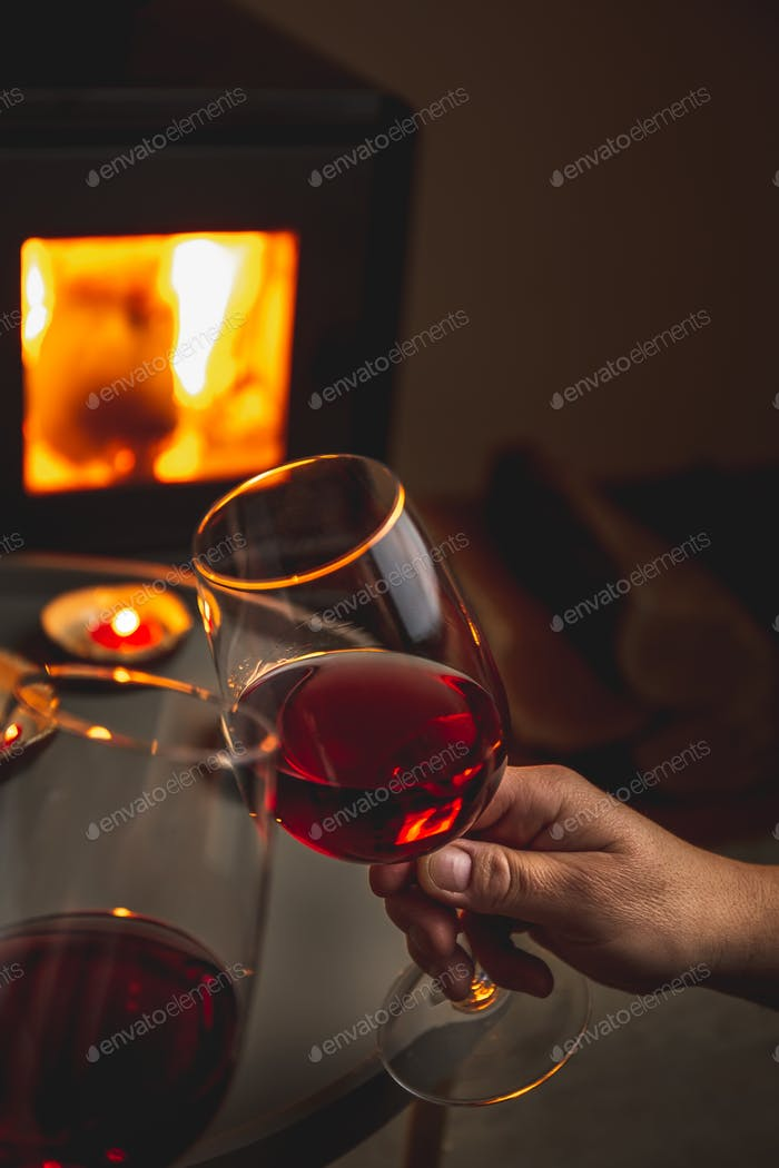 Two person holding glasses of red wine front of fireplace. Romantic light