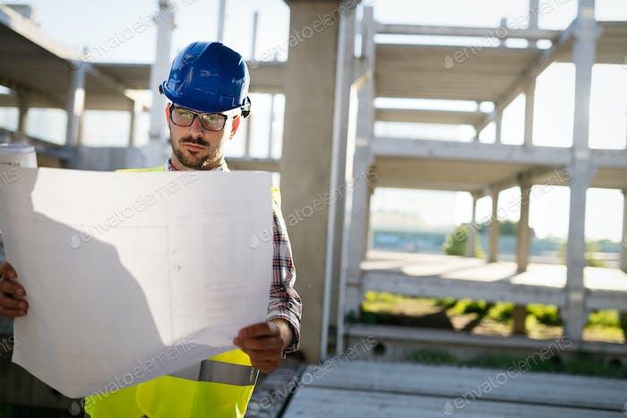 Porträt von männlichen Bauunternehmer Ingenieur mit hartem Hut hält blaues Druckpapier