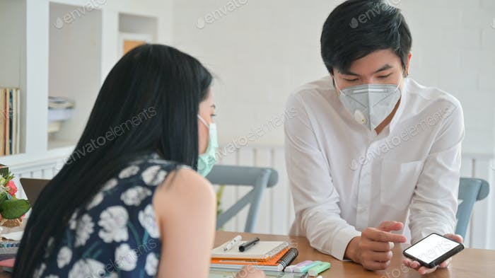 Asian women and young men wearing a mask are discussing their work at home to protect Covid-19.