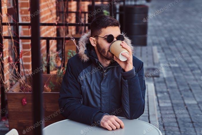 Ein hübscher junger Mann, der draußen Kaffee trinkt.