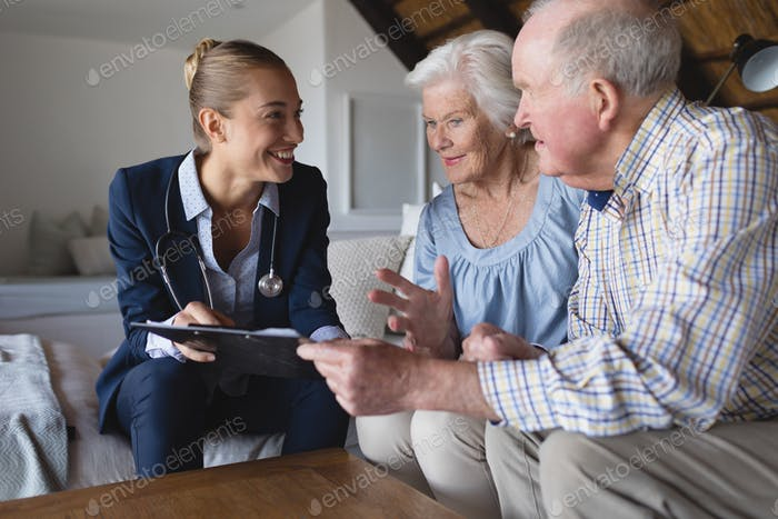 Female doctor and senior couple looking and discussing over clipboard at home
