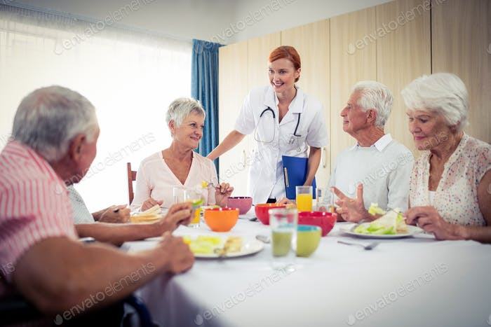 Pensioners at lunch with nurse