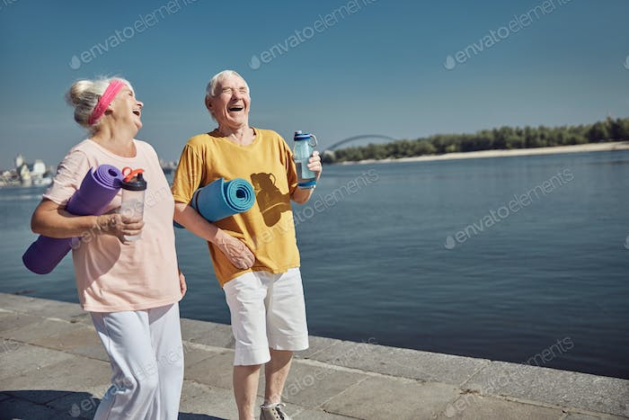 Cheerful sporty senior married people laughing outdoors