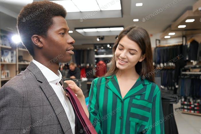 Человек в бутике выбирает галстук, улыбающийся помощник помогает