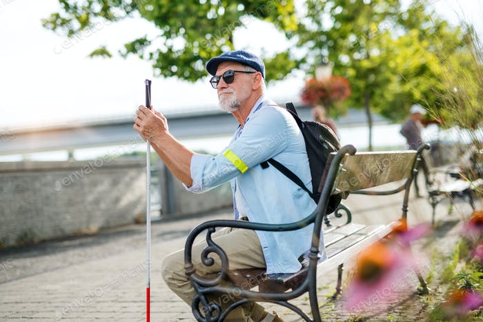 Senior blind man with white cane sitting on bench in park in city.