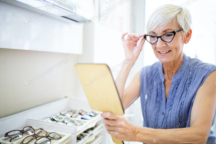 Beautiful mature woman choosing new pair of spectacles in opticians store. Eyesight correction