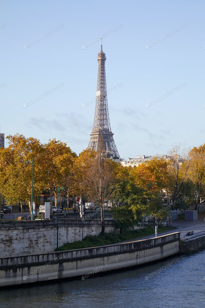 Eiffel tower and Seine river docks with autumn trees in a sunny day in Paris, France