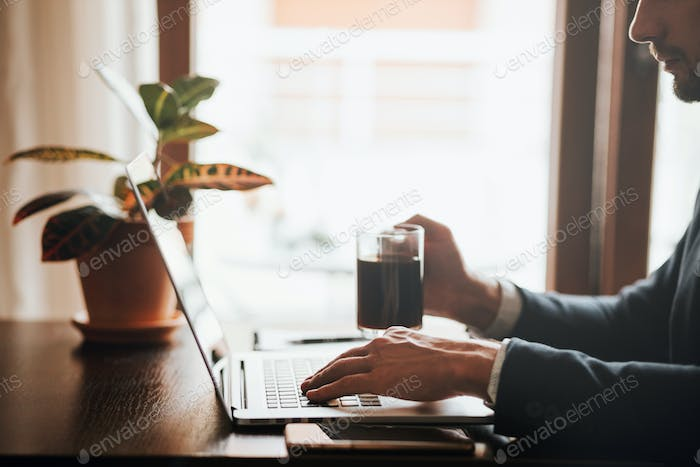 office worker typing on keyboard of laptop in office workspace deck during working day