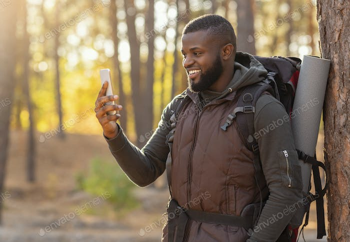 Cheerful guy taking photos of autumn forest