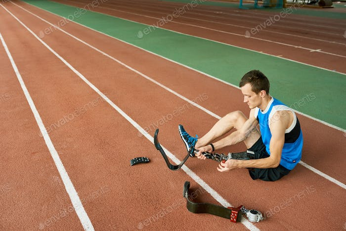 Handicapped Sportsman Fixing Artificial Limb