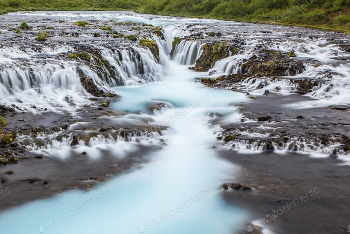 Detail of bright powerful Bruarfoss waterfall in Iceland with cyan water