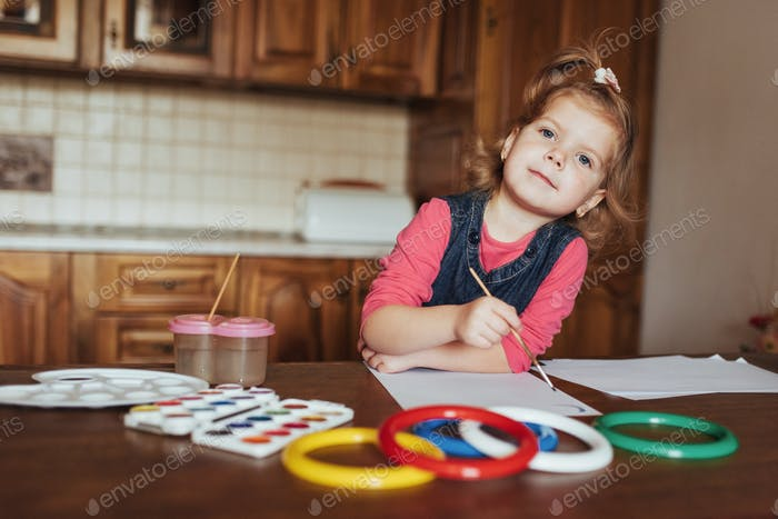 Cute little girl, adorable preschooler painting with watercolors