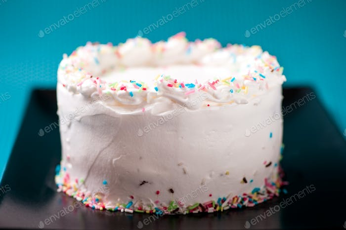 Creamy white chocolate and sweet birthday cake isolated on black