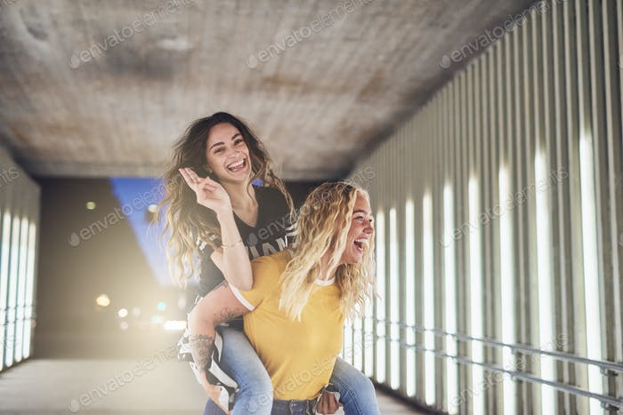 Carefree young girlfriends having fun in the city at night