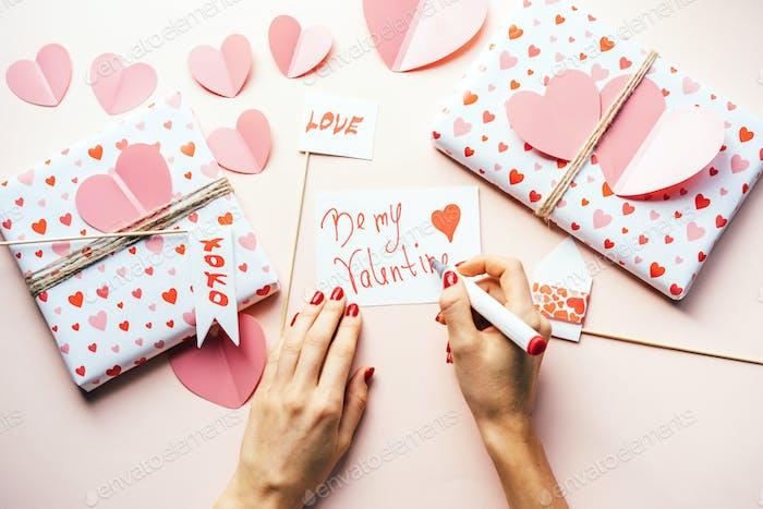 Elegante weibliche Hände mit roter Maniküre schreiben eine Notiz BE MY VALENTINE mit einem Filzstift