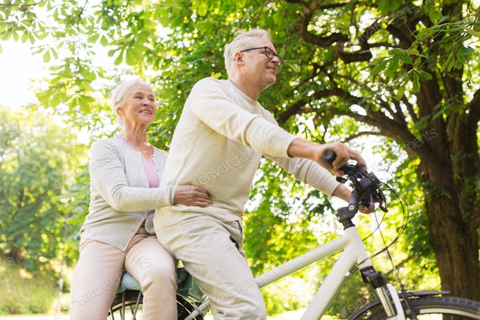 happy senior couple riding on bicycle at park