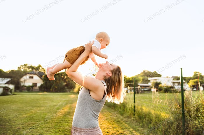 Young mother with her baby son in the garden.