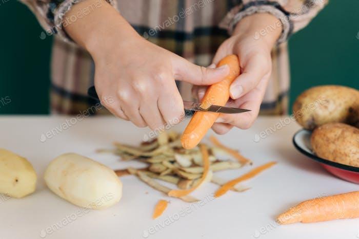 Frau schält Karotten in ihrer Küche auf weißem Marmor ab, um ihr Essen zuzubereiten.