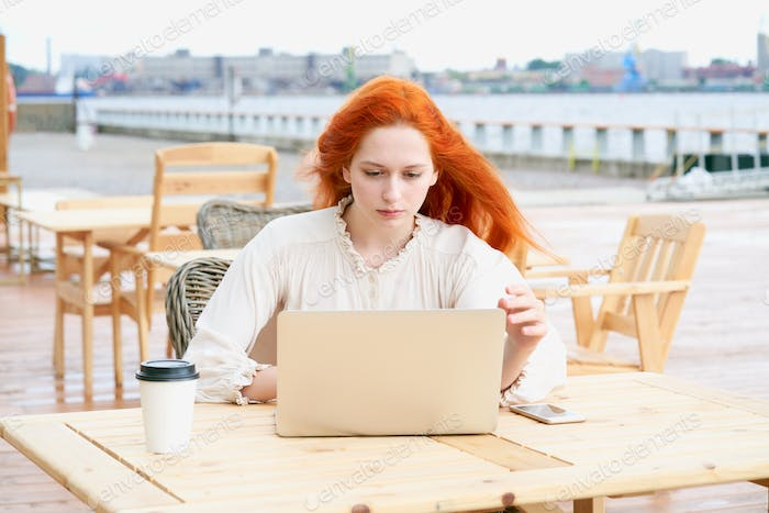 Redhead female looking at laptop in cafe outside