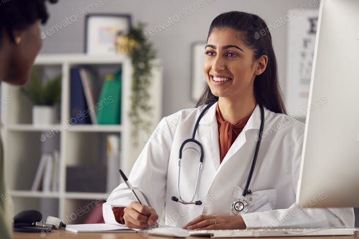 Female Doctor In White Coat Having Meeting With Woman Patient In Office