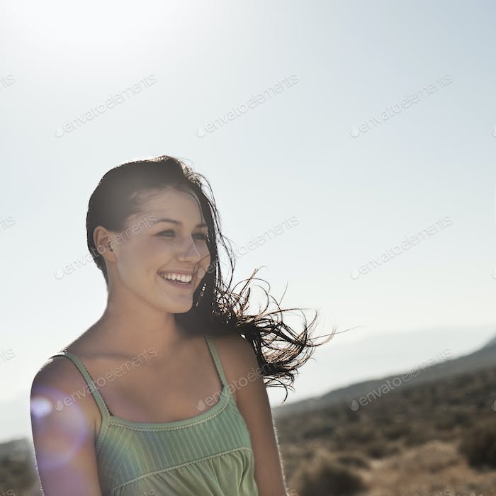 A young woman with windswept hair on the open road.