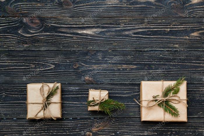 Three Vintage gift boxes with spruce branches on wooden background with copy space