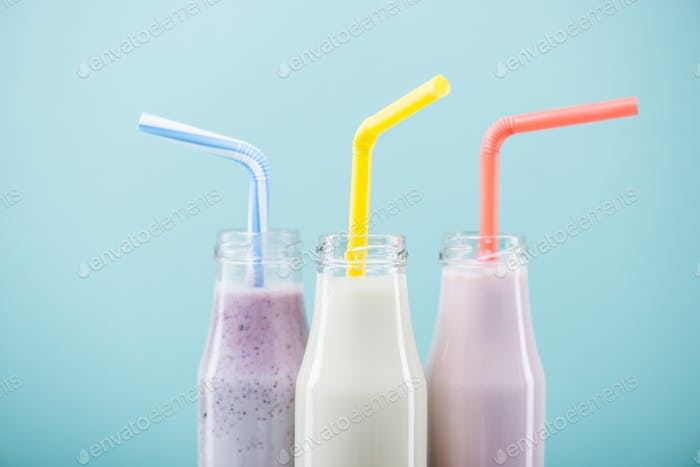 Close-up view of delicious fruity milkshakes in glass bottles with drinking straws isolated on blue