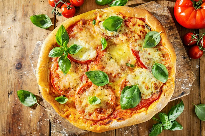Homemade pizza with mozzarella on wooden background