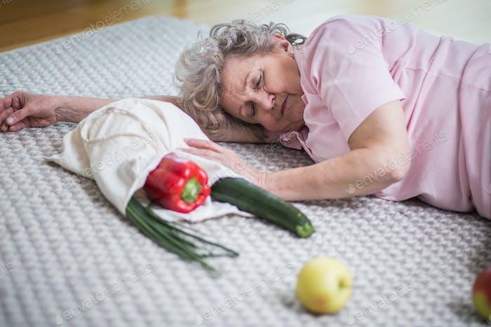 anciana acostado en el suelo junto a la bolsa de la compra con verduras