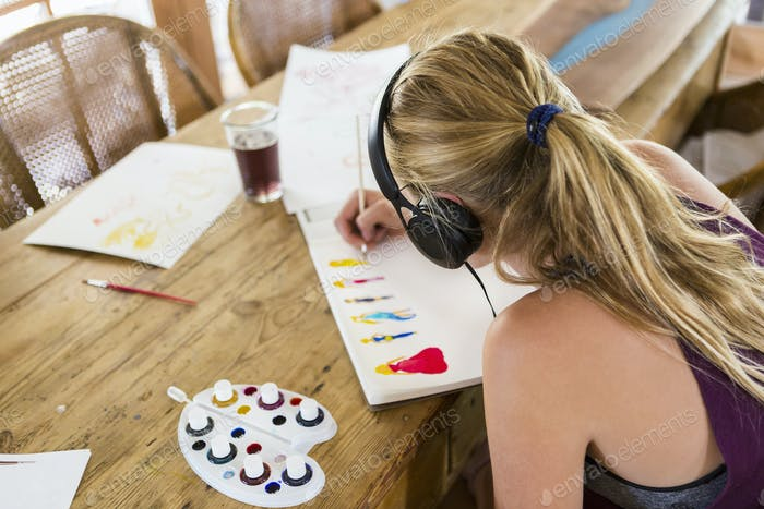 13 year old girl wearing headphones, doing watercolor sketch