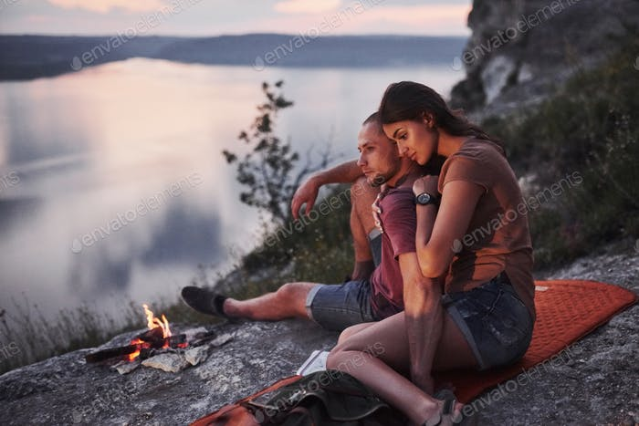 Hugging couplesitting near the fire on top of mountain enjoying view coast a river or lake