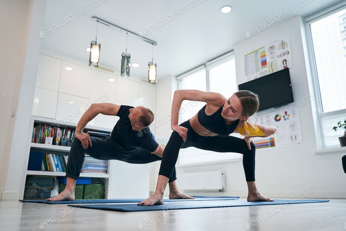 Beautiful female and neat strong man during the stretching exercises in wellness center
