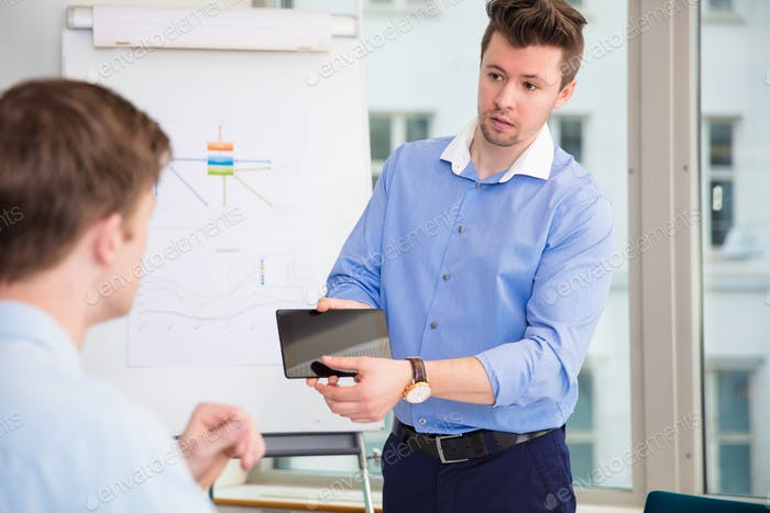Businessman Showing Digital Tablet To Male Colleague