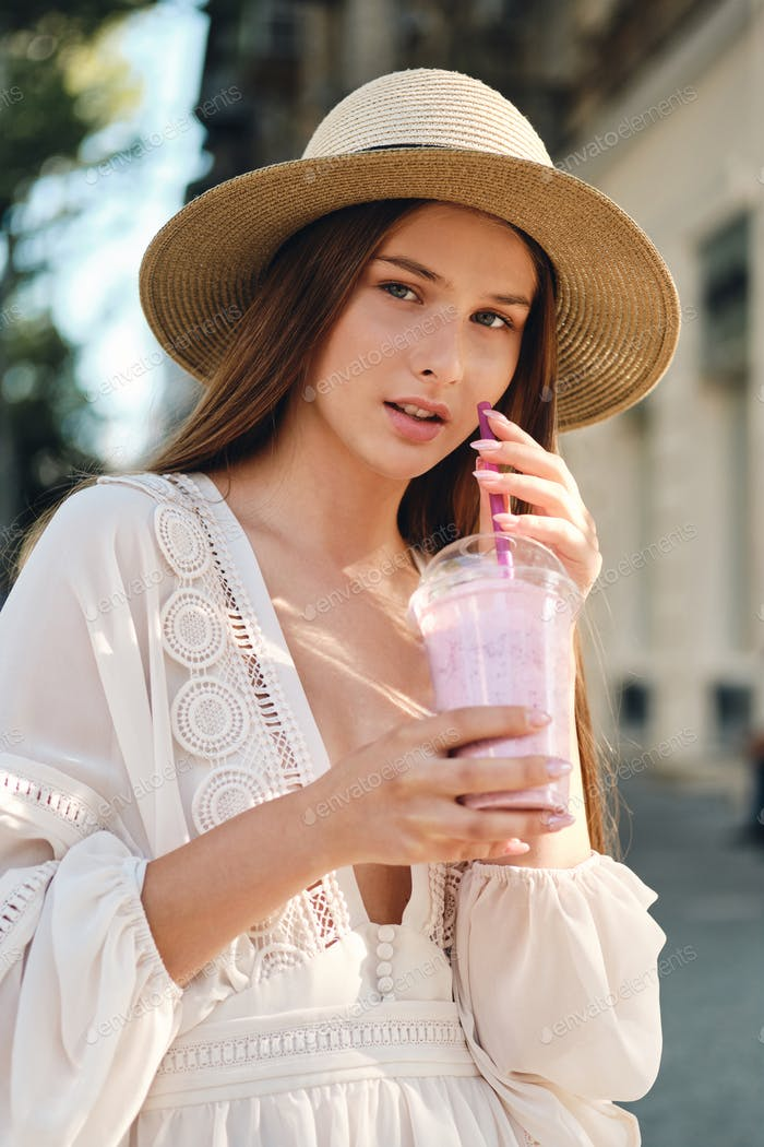 Young girl in white dress and hat holding smoothie dreamily looking in camera on cozy city street
