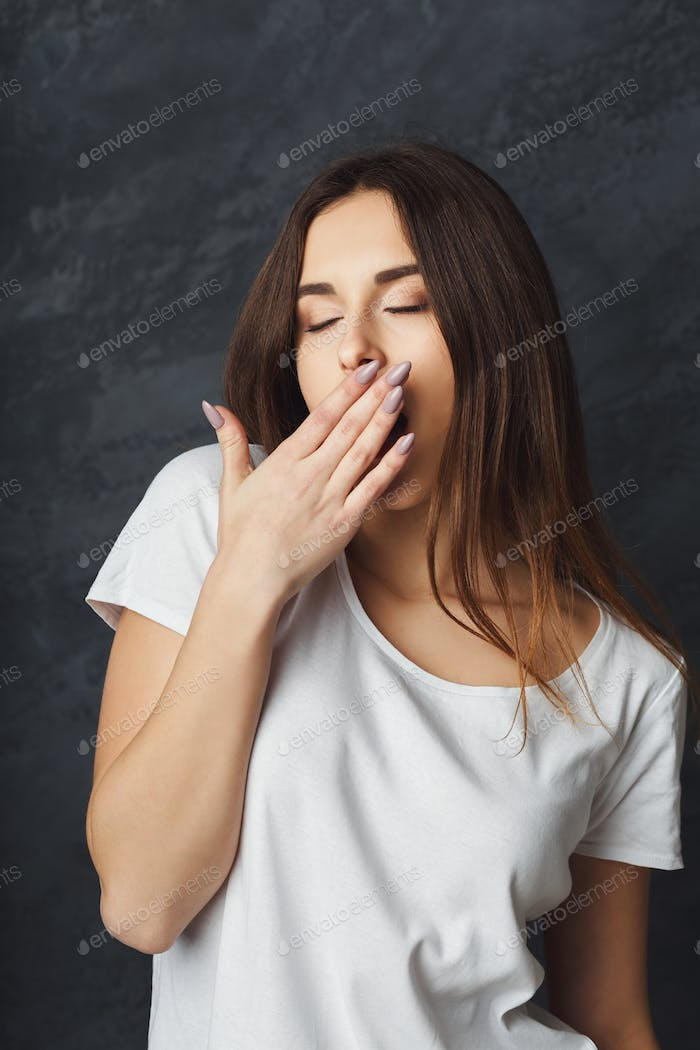 Young woman yawning on dark background