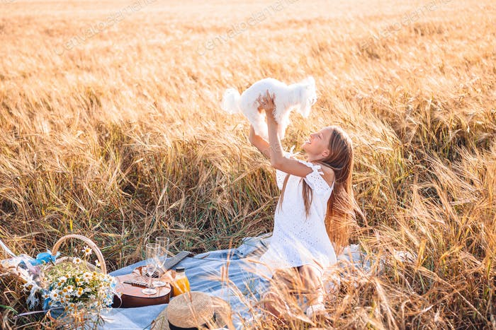 Happy child in wheat field play with dog