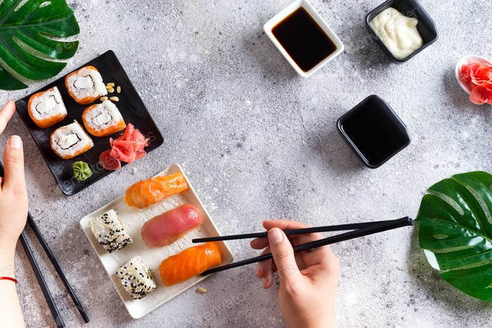 Various Fresh and delicious sushi set on black and white slate with metal and slate sticks, sauce
