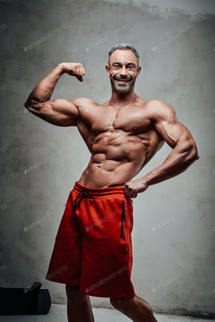 Athletic man isolated on a grey background, smiling and showing his biceps looking fresh