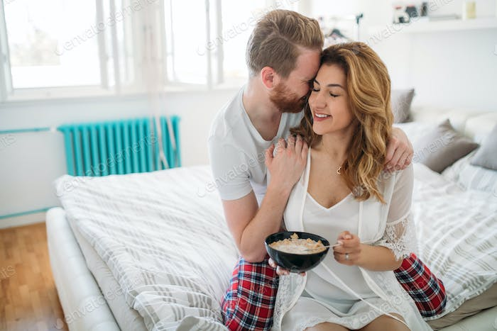 Happy married couple being romantic in bed sharing cereal
