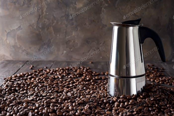 Geysir Kaffeemaschine auf dem Hintergrund der Kaffeekörner auf einem dunklen Holzhintergrund, Kopierraum