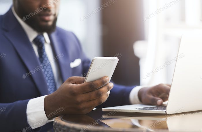 Unrecognizable African Entrepreneur Using Cellphone Working In Cafe In City
