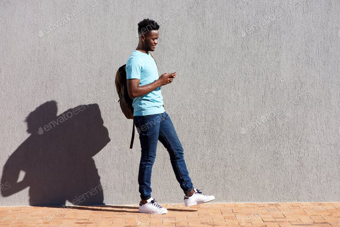 College student walking with bag and mobile phone