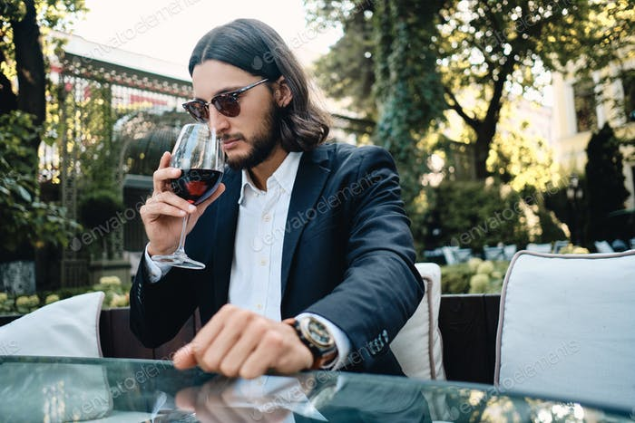 Young confident hispanic man thoughtfully sniffing glass of red wine in restaurant outdoor