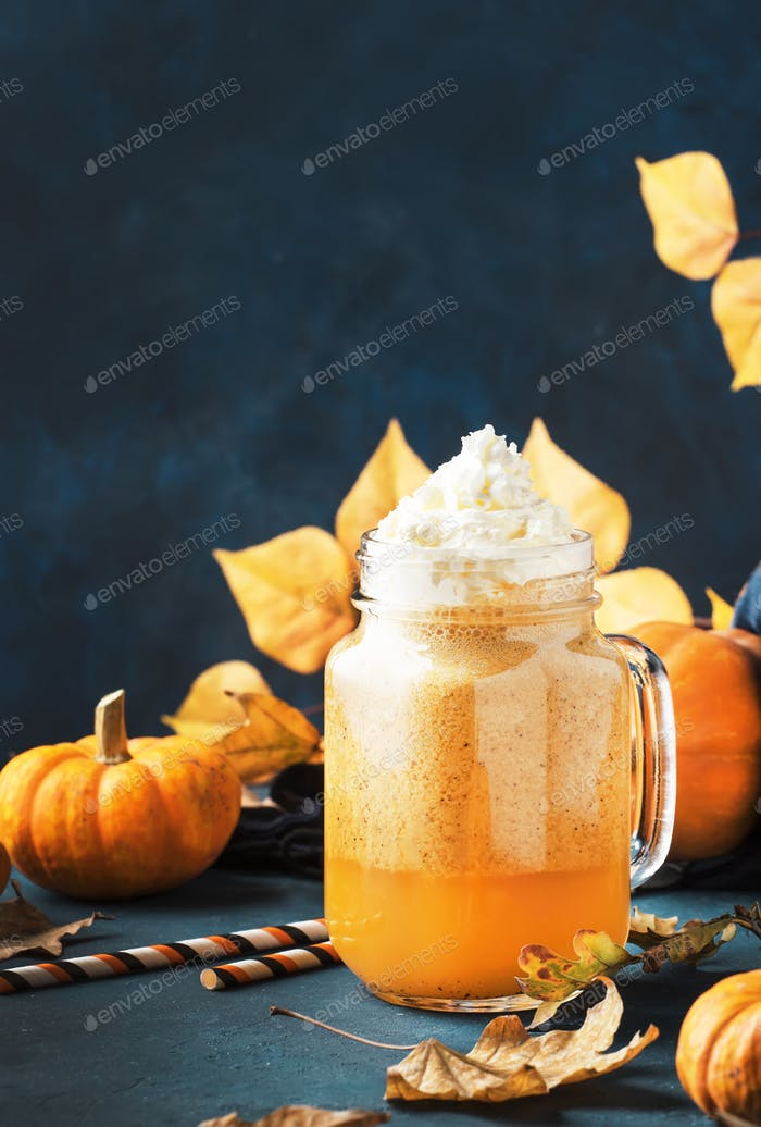 Pumpkin spiced latte or coffee in glass mug on blue table. Autumn or winter hot drink