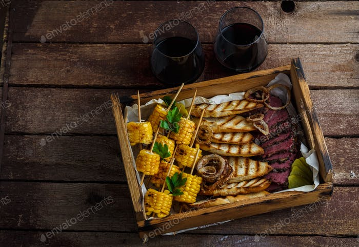 Smoked pastrami slices with grilled corn and wine