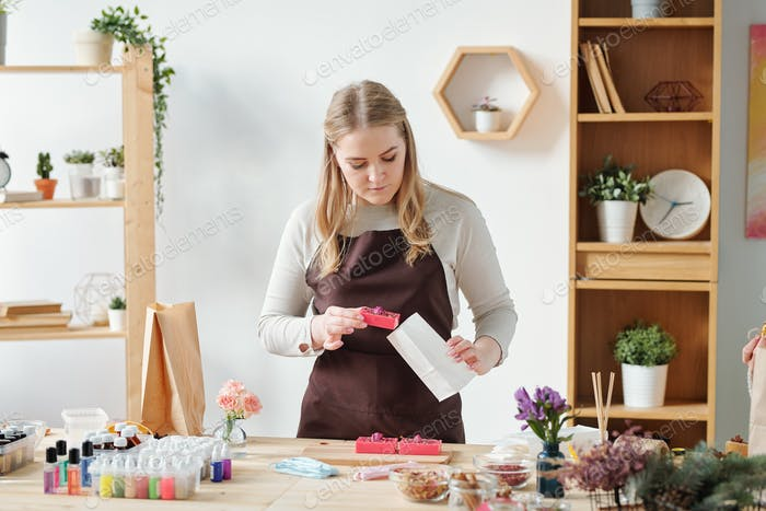 Young woman in apron putting one of handmade soap bars into paper packet