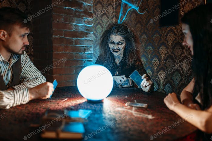 Witch reads a magic spell over a crystal ball