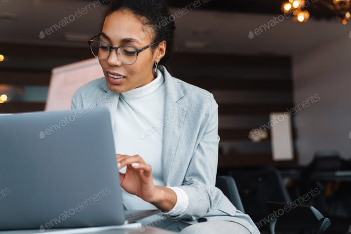 Image of african american businesswoman working on laptop in office